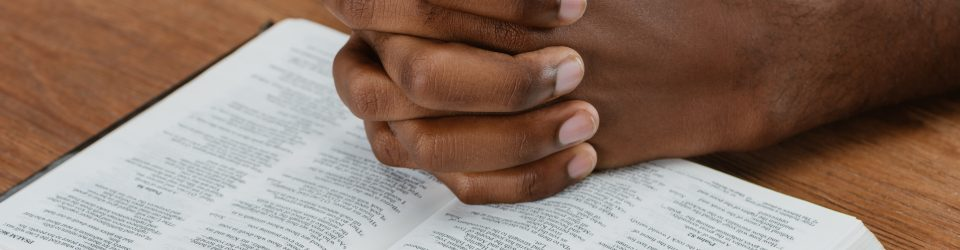 man praying with hands on bible