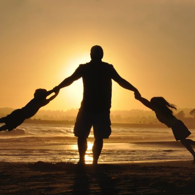 image of dad and two children on beach